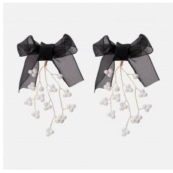 Pendientes con elegante lazo negro y colgante dorado en forma de ramas con perlas